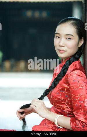 Junge Frau in traditionelle chinesische Kleidung gekleidet und hält ihr langes geflochtenes Haar, Blick in die Kamera - Stockfoto