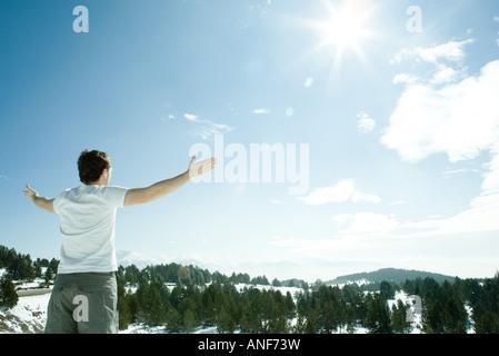 Junger Mann stehen, verschneite Berglandschaft mit Armen oben, Rückansicht - Stockfoto