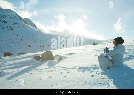 Teen Mädchen sitzen auf Schnee im Gebet Position, Sonne über Rand des Berges - Stockfoto