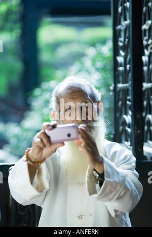 Älterer Mann tragen traditionellen chinesischen Kleidung mit Kamera-Handy - Stockfoto