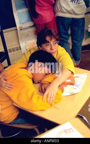 Weiße Lehrer Alter 25 tröstlich asiatisch-amerikanische Schüler Alter von 10 Jahren an der Summer School. Holland - Stockfoto