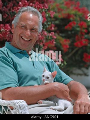 ehemaliger Alter Mann sonnte sich im Garten mit einem Kätzchen - Stockfoto