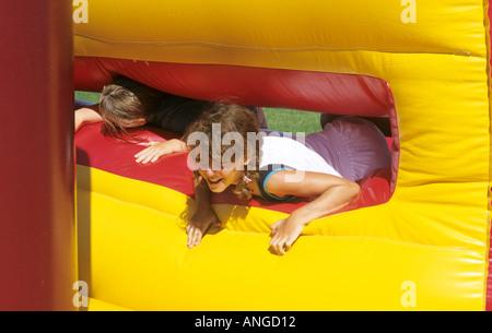 8 Jahre altes Mädchen auf aufblasbaren Hindernis-Parcours - Stockfoto