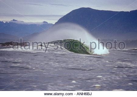 Surfer paddeln über eine Welle an der entlegenen Westküste von Vancouver Island, British Columbia, Kanada. - Stockfoto