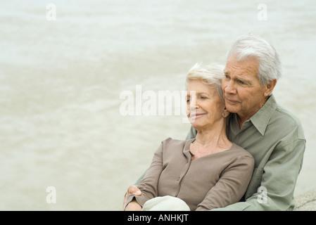 Älteres paar sitzen gemeinsam, Wange an Wange, wegschauen - Stockfoto