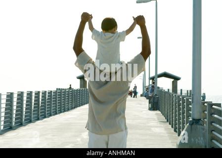 Vater mit Sohn auf Schultern, Hand in Hand, Rückansicht - Stockfoto