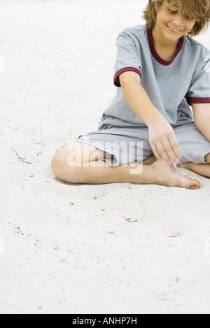 Jungen spielen im Sand, lächelnd, beschnitten Ansicht - Stockfoto