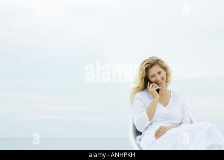 Frau sitzt im Stuhl im Freien, mit Handy, Lächeln