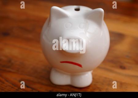 Ein unglücklich aussehenden Sparschwein um Schulden und Einsparungen zu illustrieren - Stockfoto