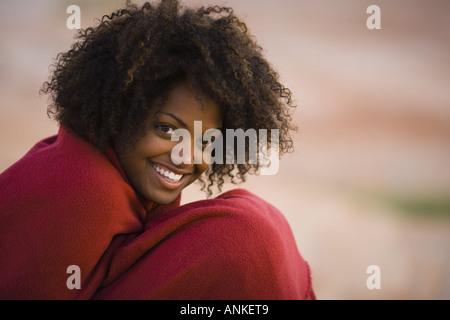 Porträt einer jungen Frau in ein Handtuch gewickelt und lächelnd - Stockfoto