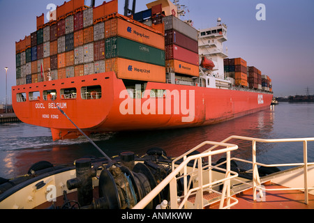 OOCL Belgien Containerschiff von Schlepper aus Southampton Docks gezogen wird - Stockfoto