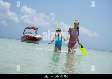 Mutter und Tochter mit Schnorcheln Ausrüstung zu Fuß im Wasser, Florida, Vereinigte Staaten - Stockfoto