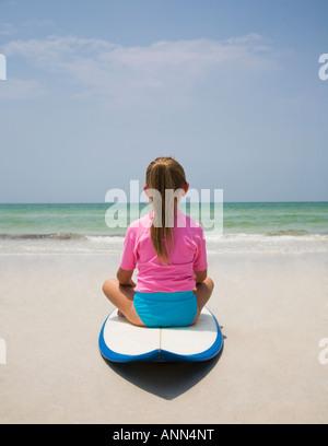 Junges Mädchen sitzt auf dem Surfbrett, Florida, Vereinigte Staaten - Stockfoto