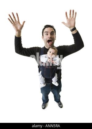 Porträt eines jungen Mannes mit seiner Tochter in einem Kabelbaum - Stockfoto