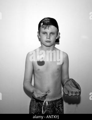Ein B&W Bild von einem 13 Jahre alten Jungen tragen eine Baseball-Cap & Mitt, fangen mit einem Baseballschläger - Stockfoto