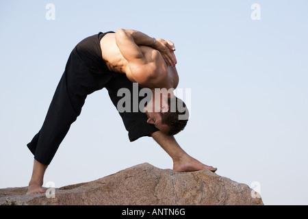Mann darstellende Hatha Yoga Parsvottanasana intensive Seite Stretch Haltung auf einem Felsen in Indien - Stockfoto