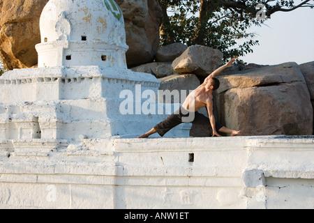 Mann, die Durchführung von Hatha Yoga Seite Stretch auf einen hindu-Tempel in Indien - Stockfoto