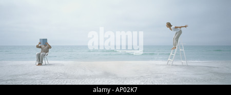 Am Strand Mann, hält Buch vor der Gesicht während die Frau auf Trittleiter schreit ihn an - Stockfoto