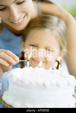 Mutter Anzünden von Kerzen auf der Geburtstagstorte für Tochter - Stockfoto
