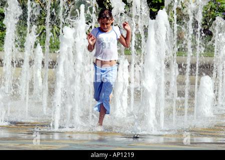 Ein junges Mädchen läuft durch den Frieden Garten Brunnen in Sheffield South Yorkshire - Stockfoto