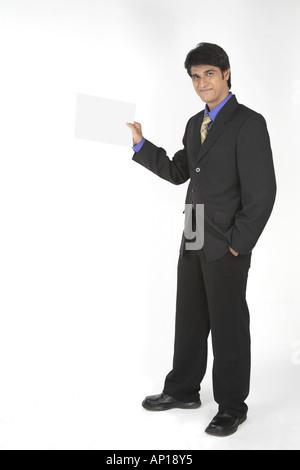 Führungskraft mit einem schwarzen Anzug stehen und halten ein leeres Blatt Papier in der hand mit einem Lächeln - Stockfoto