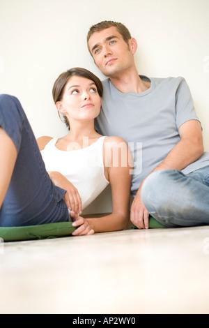 paar auf dem Boden sitzend - Stockfoto
