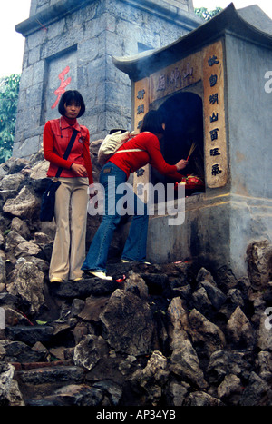 Zwei junge Frauen, die Beleuchtung Räucherstäbchen am äußeren Tempelkomplex, Hanoi, Vietnam - Stockfoto