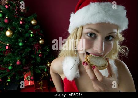 Frau in festlichen Outfit Essen traditionelle Mince Pie mit geschmückten Baum im Hintergrund - Stockfoto
