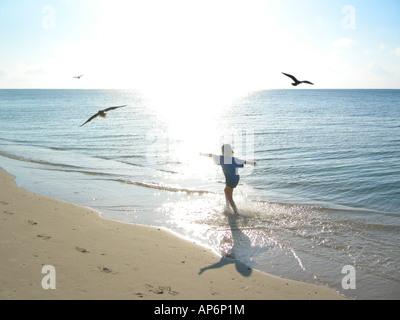 Mädchen läuft sorglos am sonnigen Strand mit Möwen fliegen - Stockfoto