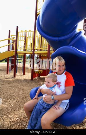 Mama und zwei Jahre alten Jungen, die Rutsche hinunter - Stockfoto