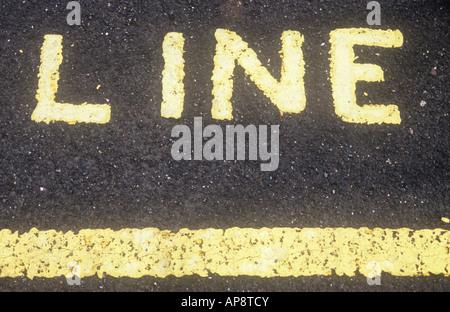 Blasse gelbe Linie gemalt auf schwarzem Asphalt und darüber das gemalte Wort LINE - Stockfoto