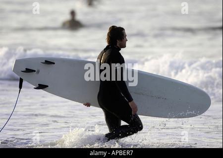 Mann im Anzug tragenden Surfbrett ins Meer am weißen Felsen Strand Portrush County Antrim-Nordirland - Stockfoto