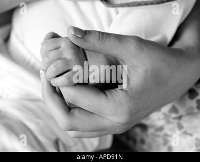 Nahaufnahme eines Babys und Väter Hände - Stockfoto