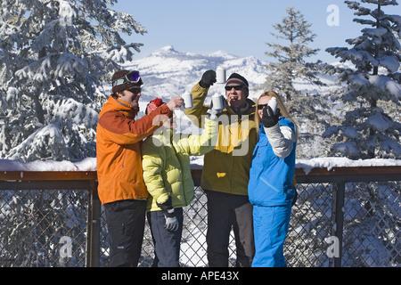 Freunde, lachen und trinken heißen Schokolade auf einem verschneiten Deck im Winter im Northstar Ski Resort in der - Stockfoto