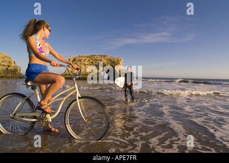 Eine Frau auf einem Cruiser-Fahrrad und ein Mann mit einem Surfbrett am Strand im Natural Bridges State Park in - Stockfoto