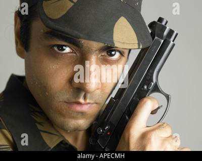 Indische Armee Soldat in wütenden Ausdruck mit Pistole - Stockfoto