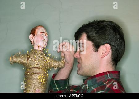 Junge männliche Künstler stecken eine Nadel in eine Voodoo-Puppe.  -MODELL VERÖFFENTLICHT. - Stockfoto