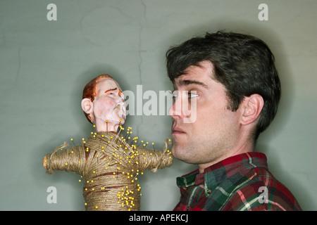 Junge männliche Künstler posiert mit einer Voodoo-Puppe.  -MODELL VERÖFFENTLICHT. - Stockfoto