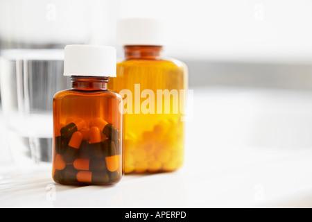 Zwei Flaschen Pillen und Glas Wasser am Tisch, Nahaufnahme - Stockfoto