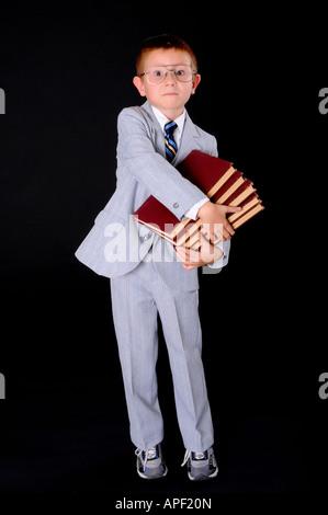 Kleiner Junge gekleidet formal trägt einen Anzug mit vielen Büchern - Stockfoto