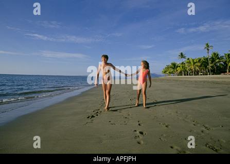 Zwei junge australische Kinder im Urlaub mit ihren Eltern gehen an einem schönen Strand in der Nähe der - Stockfoto
