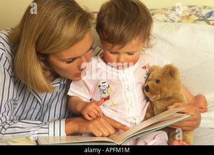 Mutter und Kleinkind zusammen ein Buch lesen - Stockfoto
