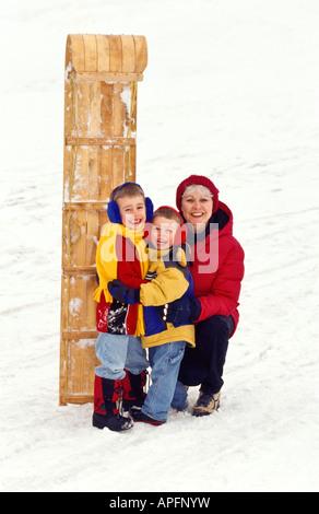 Oma und Enkel stehend mit Rodel - Stockfoto