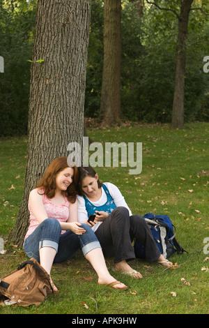 ILLINOIS Riverwoods zwei Mädchen im Teenageralter Blick auf Handy sitzen und Baumstamm gelehnt - Stockfoto
