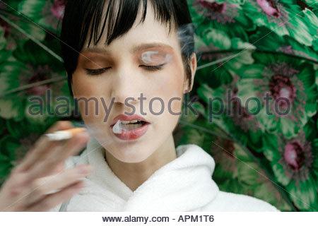 Junge Frau, die raucht, portrait - Stockfoto