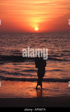 GOA, INDIEN. Ein Mann und sein kleiner Sohn gerade die Sonne über dem arabischen Meer von Benaulim Beach in der - Stockfoto