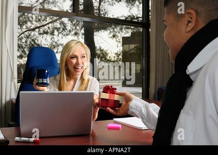 Lachend Managerin mit Kaffeetasse am Schreibtisch mit Computer und männliche Mitarbeiter erhalten ein Geschenk Box - Stockfoto