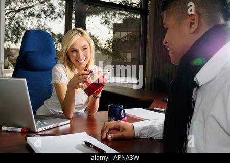 Lächelnd weiße weibliche Manager empfangenden Geschenk von schwarzen männlichen Mitarbeiter in ihrem Büro - Stockfoto