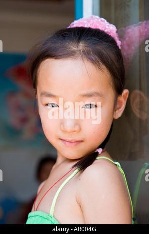 Junge asiatische orientalische Bauer Chinesin im grünen Kleid zugewandten linken Blick über Schulter Kamera China - Stockfoto