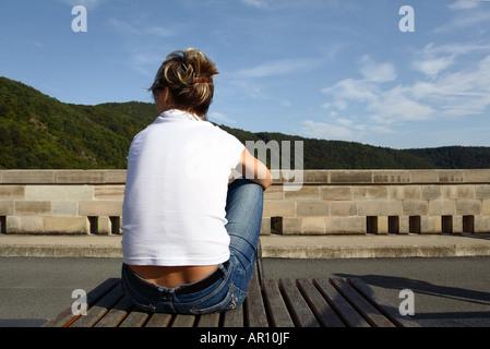 Junge Frau auf einer Bank sitzend und mit Blick auf eine Landschaft - Stockfoto